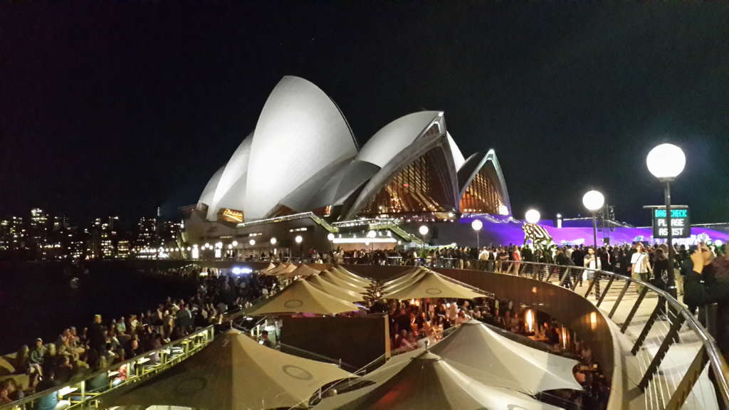 Sydney Opera house at night. Crowd watching a show.